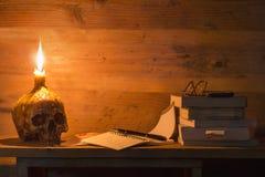头骨、书、笔、玻璃和蜡烛在木桌上在烛光 库存图片