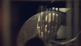 头骨和蜡烛的反射在一个老时钟的摆锤 股票录像