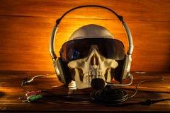 头骨在玻璃和有在老木背景的耳机的 一块人的头骨由在一个木地板上的蜡烛, H的概念点燃了 免版税库存图片