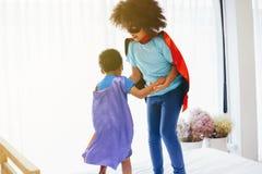 夸大和一起穿戴作为超级英雄的非裔美国人的愉快和确信的小孩在卧室 库存图片