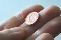 夹住一枚一欧分硬币的一个男性拇指和食指 免版税库存图片