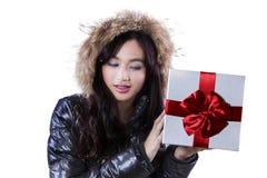 黑夹克举行礼物的女孩 免版税库存照片