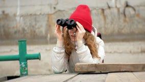 夹克和一个红色帽子的一名美丽的妇女在船坞站立并且通过双眼看 影视素材