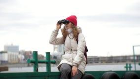 夹克和一个红色帽子的一名美丽的妇女在船坞站立并且通过双眼看 股票视频