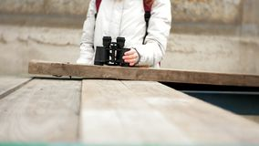 夹克和一个红色帽子的一名美丽的妇女在船坞站立并且通过双眼看 股票录像