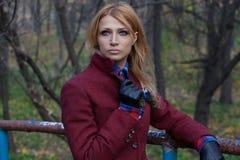 夹克和皮手套的美丽的白肤金发的妇女在秋天fo 免版税库存图片