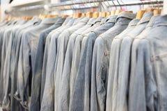 夹克在机架的牛仔裤挂衣架 库存图片