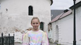 夹克步行的青少年的女孩对在古老白色墙壁背景的照相机 股票视频
