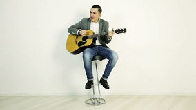 夹克的一个年轻人坐高凳并且弹一把声学吉他 股票录像