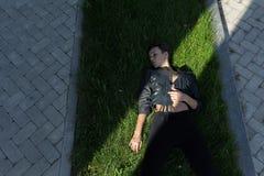 黑夹克的女孩在草 库存照片