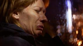夹克的妇女在汽车哭泣坐 夜和雨,背景迷离 图库摄影