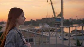 夹克的年轻姜妇女走横跨桥梁,工业工厂背景,日落的 股票录像