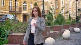 夹克的看年轻确信的姜的妇女步行沿着向下街道在城市和,黄色大厦背景 股票视频