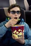 夹克的逗人喜爱的年轻人吃坐在戏院椅子的玉米花 3D玻璃的一个少年投入他的手对他的嘴和 免版税库存图片