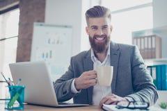 夹克饮用的咖啡的愉快的微笑的有胡子的人在morni 免版税库存照片