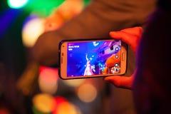夺取艺术家的表现的观众,当在阶段,使用她的电话照相机时 图库摄影