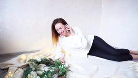 奇妙女孩与电话的恋人在格子花呢披肩地板上聊天自假日的前夕并且说谎在圣诞节花圈旁边  影视素材