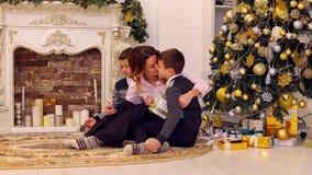 奇妙女性,两个儿子的母亲在有孪生的智能手机做selfie,坐地板在客厅,装饰 股票录像