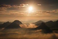 奇妙破晓 秋天在落的森林的日落视图五颜六色的谷密集的薄雾充分colred与热的太阳光芒 库存图片