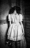 奇怪的女孩立场被转动对墙壁 查出的背面图白色 难看的东西纹理作用 免版税库存照片