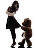 奇怪的少妇和狠毒玩具熊剪影 免版税库存图片