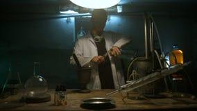 奇怪的科学家倾吐在烧瓶的液体 影视素材