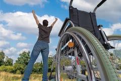 奇迹发生了 残疾有残障的人再是健康的 他是愉快和身分在草甸在他的轮椅附近 免版税图库摄影