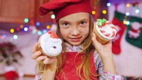 奇迹美丽的厨师女孩保持平衡在照相机用圣诞节杯形蛋糕 股票录像