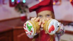 奇迹美丽的厨师女孩保持平衡在照相机用圣诞节杯形蛋糕 影视素材