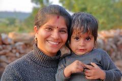 奇陶尔加尔,拉贾斯坦,印度- 2017年12月13日:一名美丽的微笑的妇女的画象有她的小男孩的 免版税库存图片