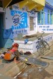 奇陶尔加尔,拉贾斯坦,印度- 2017年12月14日:与一名妇女的街道场面有五颜六色的在她的h前面的礼服洗涤的衣裳的 免版税库存照片