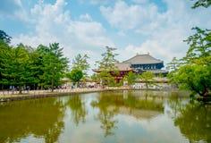 奈良,日本- 2017年7月26日:未认出的人民走到有后边一个东部伟大的寺庙的Todai籍寺庙的和a 免版税库存照片