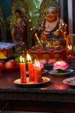 奉献的蜡烛和香火,与菩萨 免版税库存照片