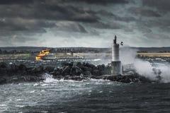 奋斗在多暴风雨的天气的黄色船 免版税库存照片
