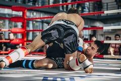 奋斗在混杂的武术的两位运动员之间在圆环地板上的  免版税库存照片