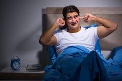奋斗从噪声的年轻人在床上 免版税库存照片