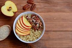 奎奴亚藜早餐粥 素食奎奴亚藜粥用新鲜的苹果和山核桃果在一个白色碗和在木背景 库存图片