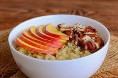 奎奴亚藜粥用新鲜的苹果和胡说的顶部 素食奎奴亚藜粥用苹果和山核桃果在一个白色碗 免版税库存照片