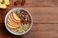 奎奴亚藜粥用果子和胡说的顶部 素食主义者奎奴亚藜粥用苹果和山核桃果在一个白色碗 免版税库存照片