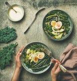 奎奴亚藜,无头甘蓝,豆,鲕梨,与乳脂状的tahini的鸡蛋穿戴碗 免版税库存照片
