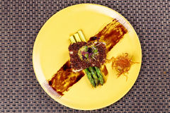 奎奴亚藜用硬皮覆盖了在芦笋的鱼在黄色板材 免版税库存照片