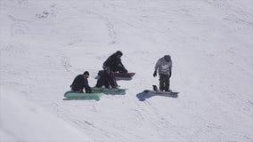 索契,俄罗斯- 2016年4月2日:挡雪板坐在滑雪胜地的倾斜 晒裂 多雪的山 极其体育运动 股票视频