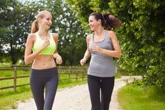 奔跑的两个女性朋友在一起乡下 免版税图库摄影