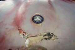 奔驰车敞篷象征在一个生锈的身体的 免版税库存图片