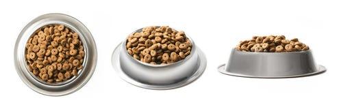 套三个盘烘干在白色背景隔绝的金属碗的宠物食品 上面,半和正面图 库存图片