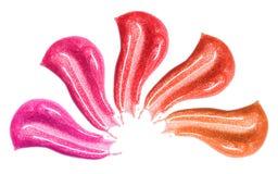 套不同的嘴唇光泽抹上在白色隔绝的样品 被弄脏的构成产品样品 图库摄影