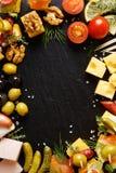 套不同的鲜美开胃菜、快餐和成份在黑背景 免版税库存图片