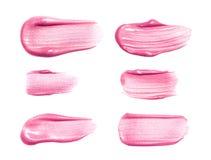 套不同的嘴唇光泽抹上在白色隔绝的样品 被弄脏的构成产品样品 免版税库存图片