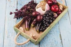 套不同的紫罗兰色新鲜的未加工的蔬菜和果子在木盘子,顶视图 免版税库存照片