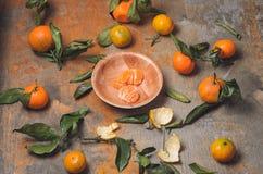 套与叶子在老木背景,几个被清除的腹片的新鲜的蜜桔 免版税库存图片